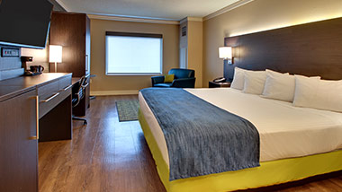 hotel room with king bed, tv, office desk, sitting chair