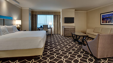 hotel room with king bed, couch, tv, sitting chair, office desk