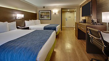 hotel room with two queen beds, office desk, and tv