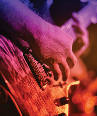 Hands strumming the strings of an electric guitar with a purple and orange color overlay.