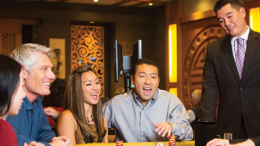 players and asian casino host at a gaming table