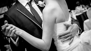 Close-up black-and-white picture of the arms and torsos of a groom and bride dancing.