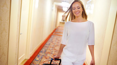 walking down hotel hallway with suitcase