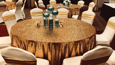 Round table with gold tablecloth, teal votive, and cream chair covers.