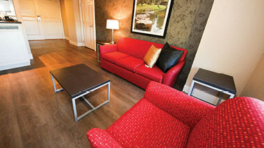 A red armchair and couch with wooden coffee table inside the living area of the Sunset 2Bay Suite at Hollywood Casino hotel in St. Louis, Missouri.