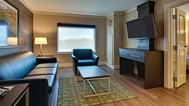 hotel suite with couch, sitting chair, tv