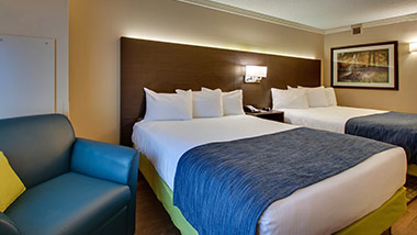 hotel room with two queen beds and sitting chair