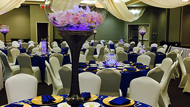 A wedding reception featuring table rounds and tall fish bowl centerpieces in white and dark blue.