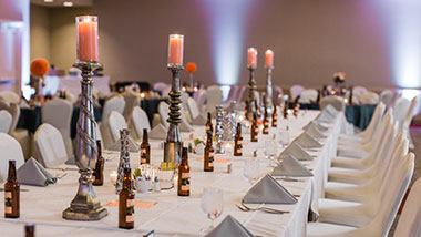 A family-style reception setup featuring long tables in white linen with tall candle sticks down the center.