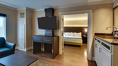 hotel suite with tv, wet bar, bedroom