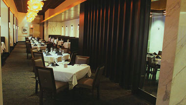 A long row of tables  set for 4 each inside Final Cut Steakhouse at Hollywood Casino in St. Louis, Missouri.