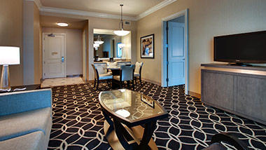 Hotel suite with couch, tv, coffee table, dining table