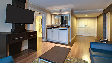 hotel suite with couch, tv, wet bar