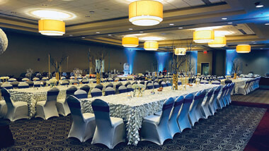 Long rectangle banquet tables with decorative table cloths and spandex chair covers.