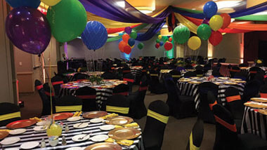 Multi-colored material is draped from the ceiling above multi-colored balloons and several round tables with black-and-white striped table cloths inside the banquet space at Hollywood Casino in St. Louis, Missouri.