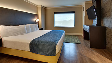 hotel suite with king bed, tv